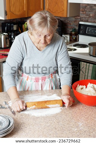 Senior woman or grandma rolling dough to make pies in her kitchen - stock photo