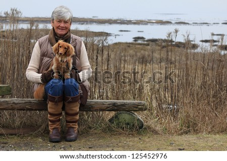 Senior woman outside with her dachshund dog. - stock photo