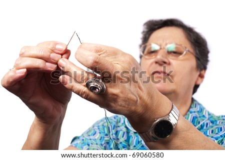Senior woman passing the string through needle for sewing - stock photo