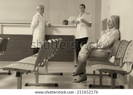 Senior woman patient seated in the hospital waiting room with medical personnel at the desk. - stock photo