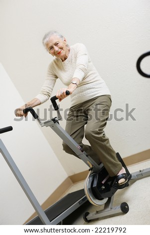 Senior woman pedaling on stationery bike - stock photo