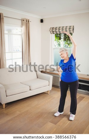 Senior woman performing stretching exercise at home - stock photo
