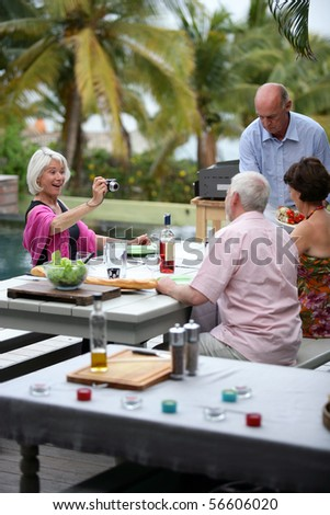 Senior woman photographing a senior man during a barbecue - stock photo