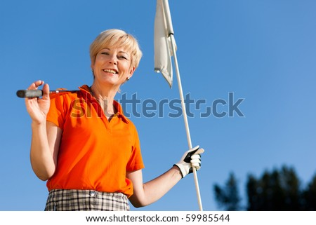 Senior woman playing golf holding the flag in her hand - stock photo