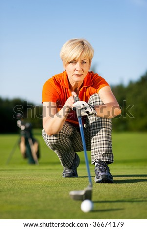 Senior woman playing golf looking and aiming for the hole - stock photo