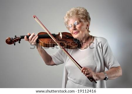 senior woman playing violin - stock photo