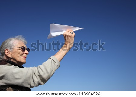 Senior woman playing with paper plane over blue sky. - stock photo