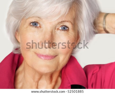 Senior woman portrait  with white hair and  red blouse, holding left arm on the side and has the hand in her hair - stock photo