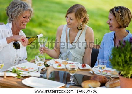 Senior woman pouring wine in glass for daughter at dining table in lawn - stock photo