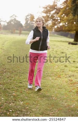 Senior Woman Power Walking In The Park - stock photo