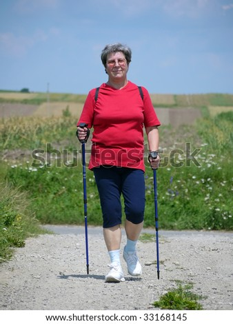 Senior woman practicing nordic walking in the countryside - stock photo