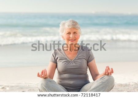 Senior woman practicing yoga on the beach