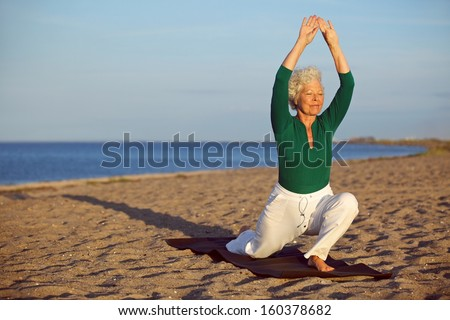 Senior woman practicing yoga poses on the sandy beach. Elder caucasian woman stretching legs and arms on the seashore. Healthy lifestyle and fitness concept - stock photo