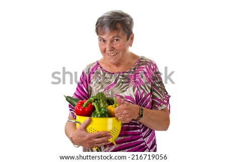 Senior woman presenting a basket of vegetables - isolated - stock photo