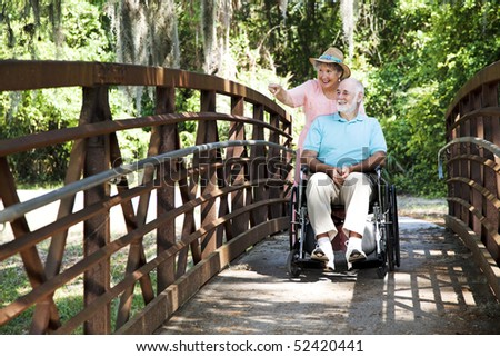 Senior woman pushing her disabled husband through the park in his wheelchair. - stock photo