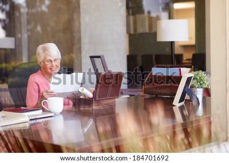 Senior Woman Putting Letter Into Keepsake Box - stock photo