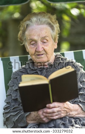 Senior woman reading a book sitting in the garden. - stock photo