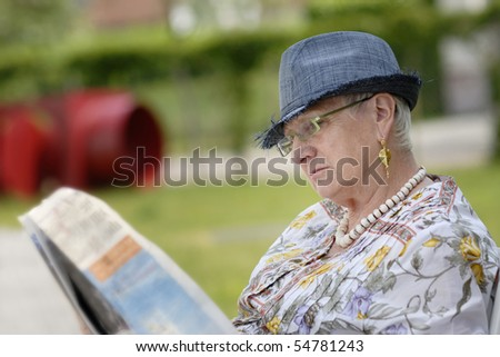 senior woman reading a newspaper in the garden - stock photo