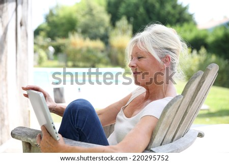 Senior woman reading book by swimming-pool - stock photo