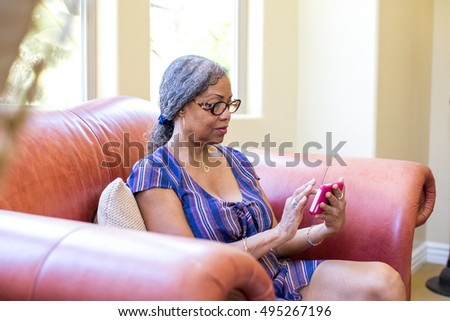 Senior Woman reading email on mobile device at home