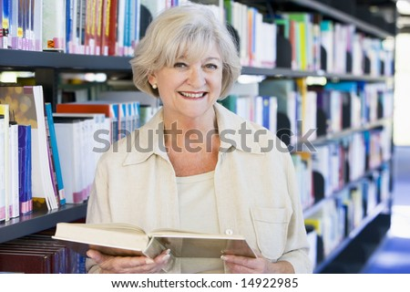 Senior woman reading in a library - stock photo