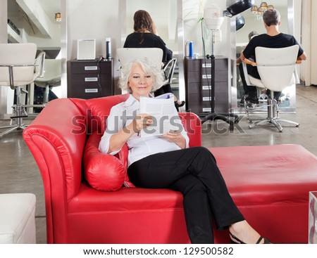 Senior woman reading magazine with clients waiting for hairdresser at parlor