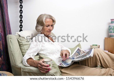 Senior woman reading newspaper while relaxing at home - stock photo