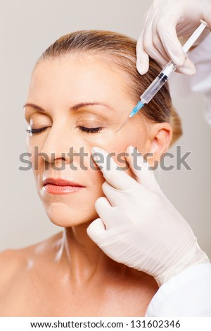 senior woman receiving plastic surgery injection on her face - stock photo