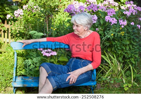 Senior Woman Relaxing at the Blue Wooden Garden Bench While Looking at the Left Frame. - stock photo