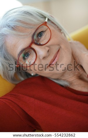Senior woman relaxing in armchair reading book