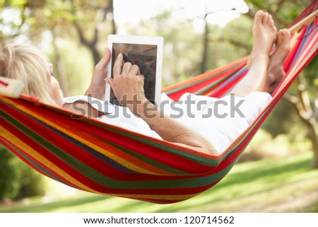 Senior Woman Relaxing In Hammock With  E-Book - stock photo