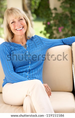 Senior Woman Relaxing On Sofa At Home - stock photo
