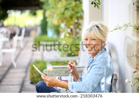 Senior woman relaxing outside and using tablet - stock photo