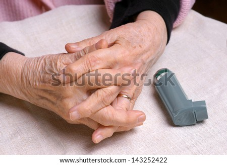 Senior woman's hands and asthma inhaler - stock photo