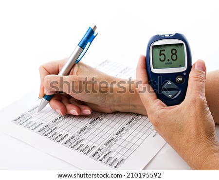 senior woman's hands writing data from glucometer to medical form on white background - stock photo