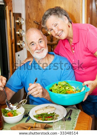 Senior woman serves a healthy dinner to her husband in their modern motor home. - stock photo