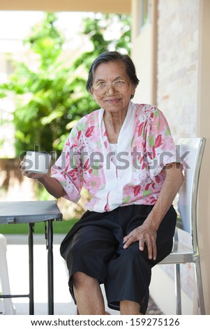 senior woman seventy years old with good healthy life and a white cup of hot water with relaxing emotion sitting on desk at home terrace and smiling - stock photo