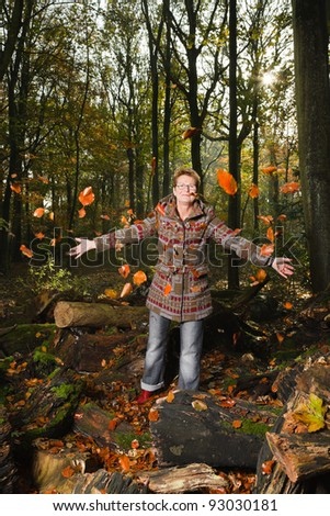 Senior woman short blond hair wearing glasses and red brown winter coat standing in autumn forest playing with leafs
