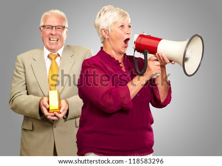 Senior Woman Shouting In Megaphone In Front Of Businessman Holding Gold Bar On Gray Background - stock photo