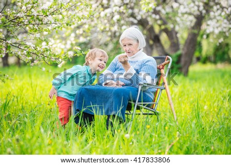 Senior woman showing something in hand to great grandson while relaxing in blossoming orchard - stock photo