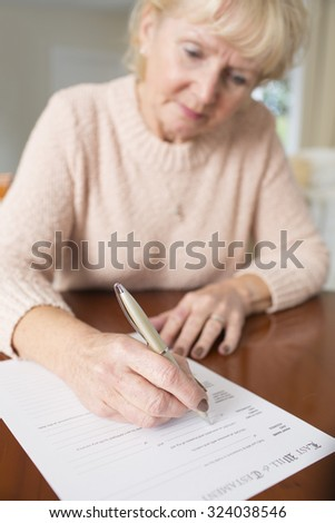 Senior Woman Signing Last Will And Testament At Home - stock photo