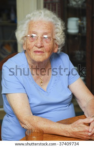 Senior woman sitting at a table looking off to one side