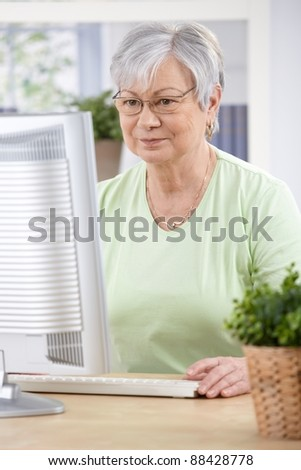 Senior woman sitting at desk, browsing internet at home.? - stock photo