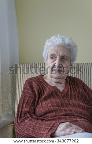 senior woman sitting in an armchair in home