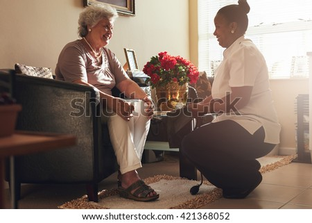 Senior woman sitting on a chair at home with female caregiver holding blood pressure gauge.  Female nurse visiting senior patient for checking blood pressure. - stock photo