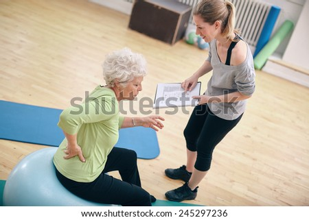 Senior woman sitting on a fitness ball with her female instructor explaining exercise plan at gym. Physical therapist with old woman at rehab. - stock photo
