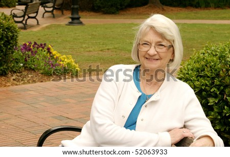 Senior woman sitting on a park bench - stock photo