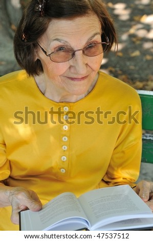 Senior woman sitting on bench reading book outdoors in park - stock photo