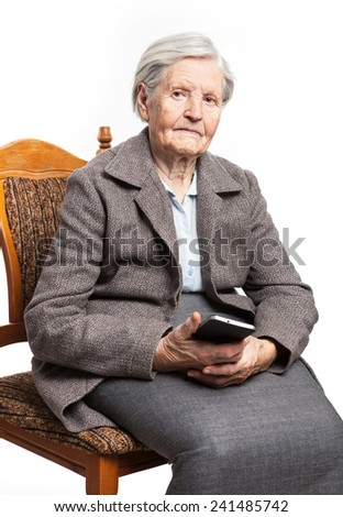 Senior woman sitting on chair and holding mobile phone  - stock photo