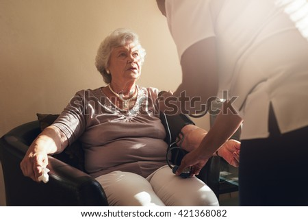 Senior woman sitting on chair at home and nurse measuring her blood pressure. - stock photo